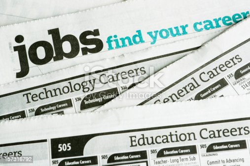 Newspaper job listing pages, stacked to illustrate job search and employment opportunities and the job hunting process of looking for careers and occupations in the classified ad section of printed papers. For concepts of unemployment, employment issues, recession, economic depression, recovery, job seeking and discovery. Horizontal image with no people.