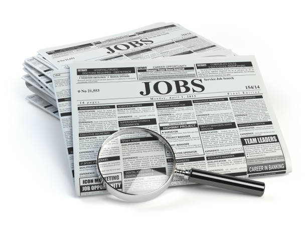 Job search. Loupe with jobs classified ad newspapers stock photo