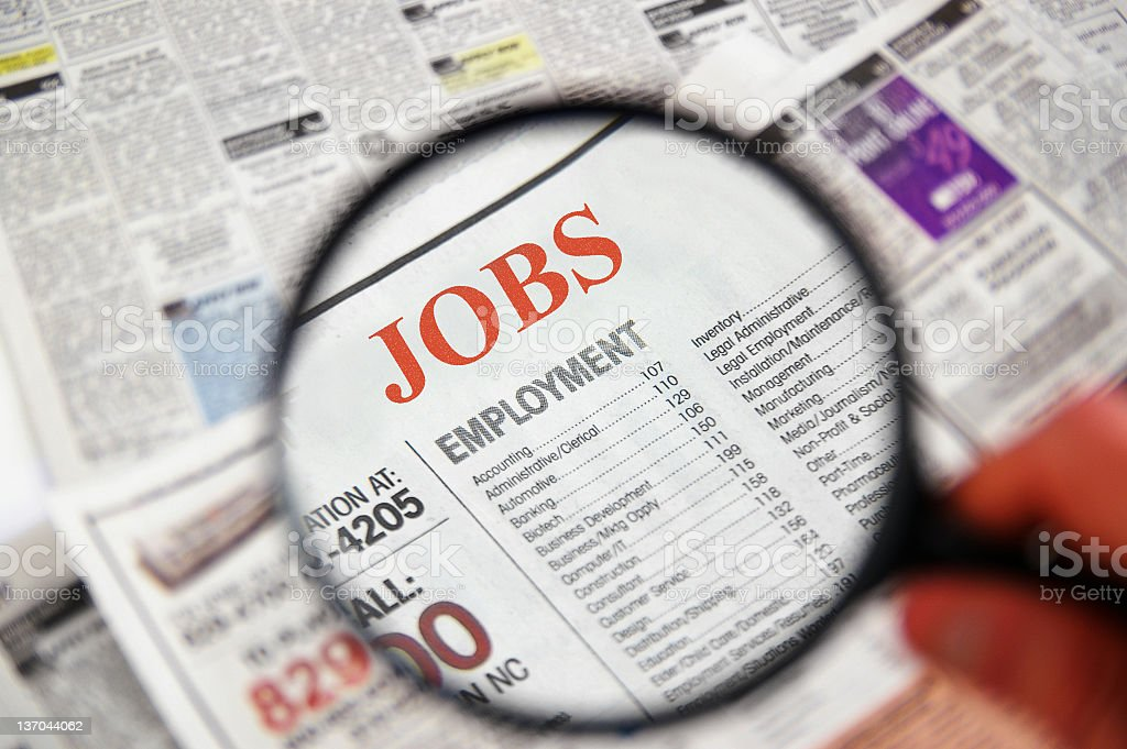 Job searching on newspaper using magnifier stock photo