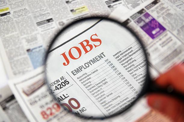 job searching on newspaper using magnifier - unemployment stock pictures, royalty-free photos & images