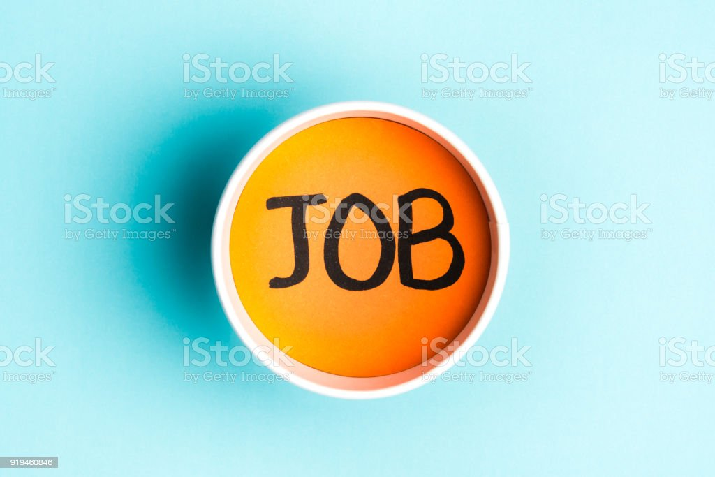 Job text orange into paper cup over blue background stock photo