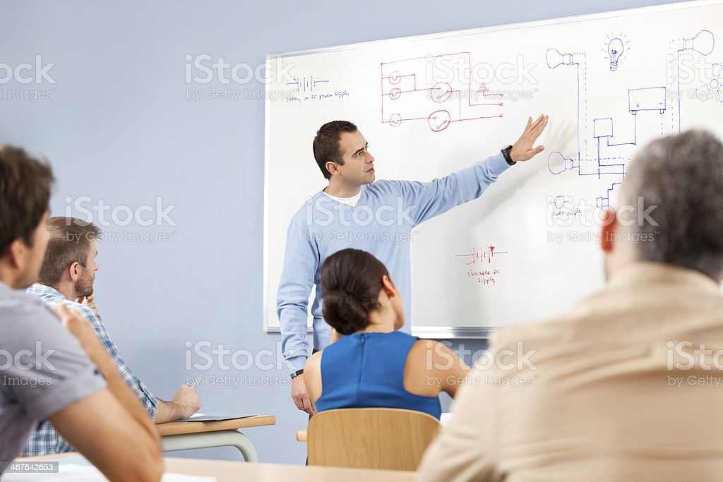 Job training Group of adult student attending a job training. Male teacher explaining diagrams technical systems drawn on whiteboard. 30-39 Years Stock Photo