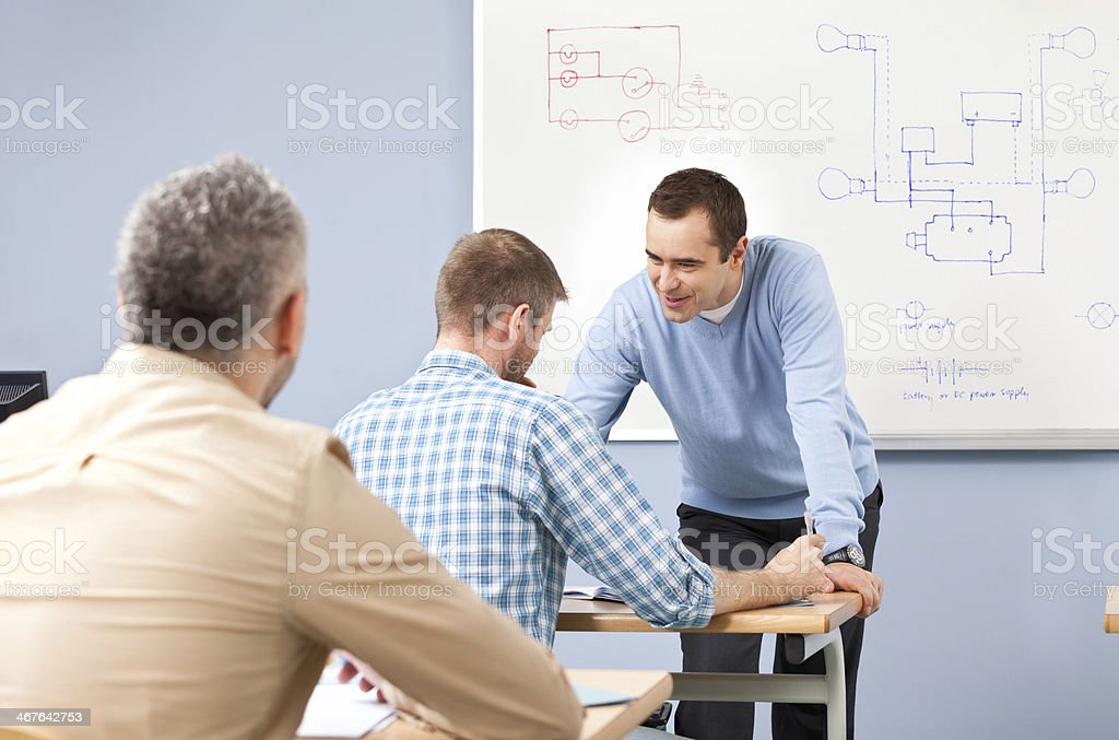 Job training Group of adult student attending a job training. Male teacher talking with a student. 30-39 Years Stock Photo