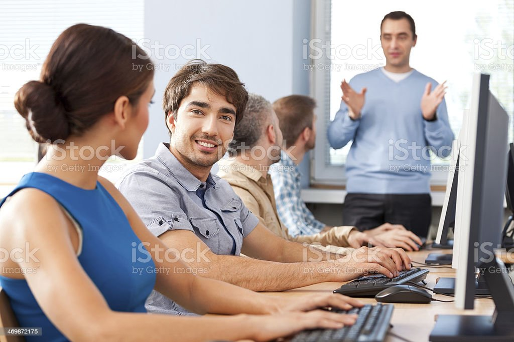 Job training Group of adult students attending computer course. Focus on man wearing blue shirt smiling at camera. 30-39 Years Stock Photo