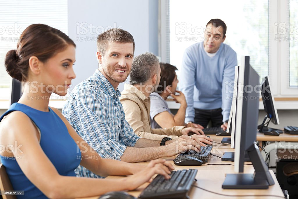 Job training Group of adult students attending computer course. Focus on man with beard smiling at camera. 30-39 Years Stock Photo