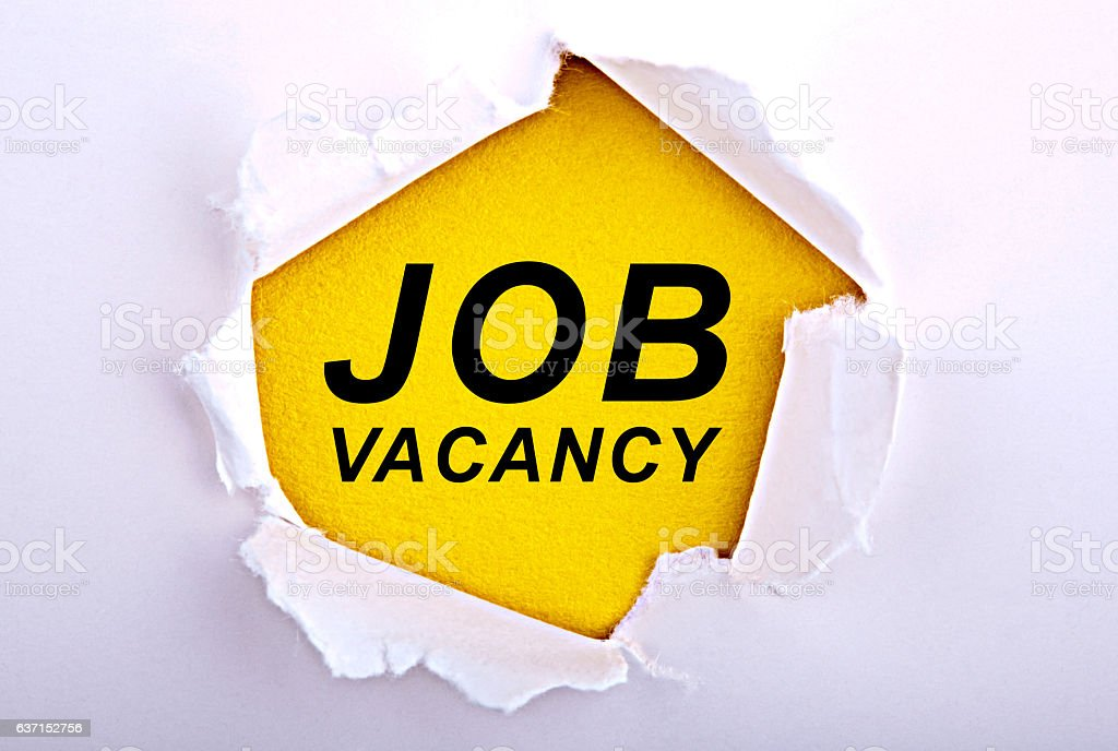 Job Vacancy text under ripped paper. stock photo