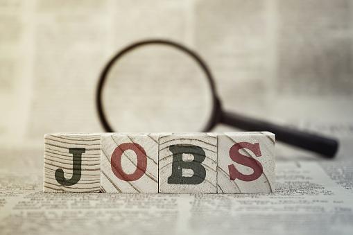 Opportunità Di Lavoro In Legno Isolato E La Lente D Ingrandimento Su Sfondo Di Giornale - Fotografie stock e altre immagini di Affari