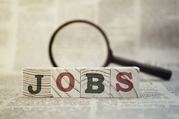 """""""jobs"""" on wooden block and magnifying glass on newspaper background - employment issues stock photos and pictures"""