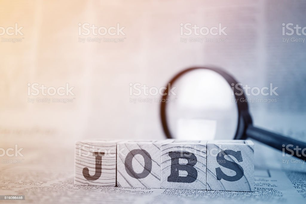 'Jobs' on wooden block and magnifying glass on newspaper background​​​ foto