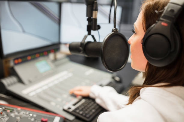 Jockey Wearing Headphones While Using Microphone In Radio Statio Young female jockey wearing headphones while using microphone in radio station radio dj stock pictures, royalty-free photos & images