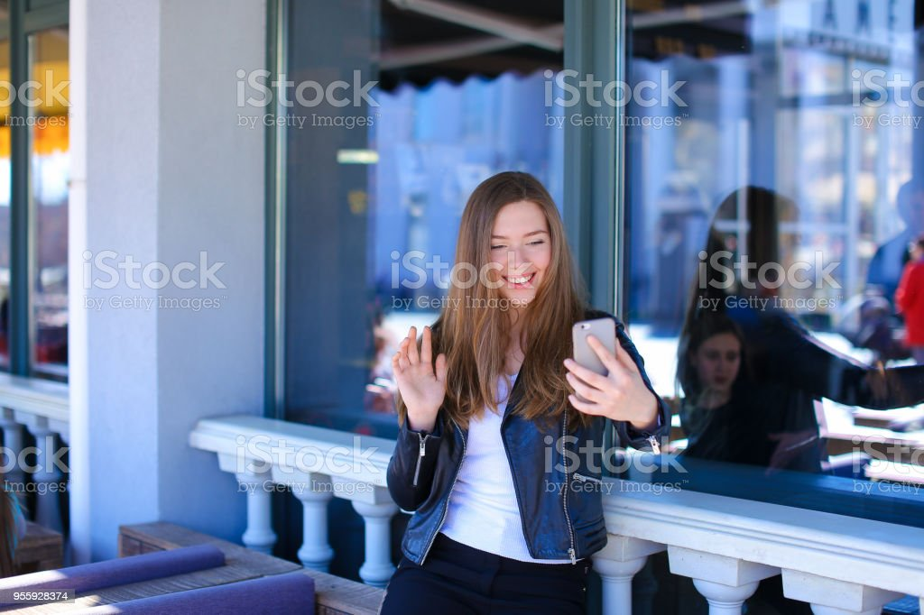 Jocund female peson making video call by smartphone at street cafe stock photo