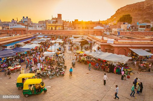 The beautiful market in Jodhpur's Old City. People are visible in the image, walking standing or sitting in their rickshaws as it is the case in the foreground.