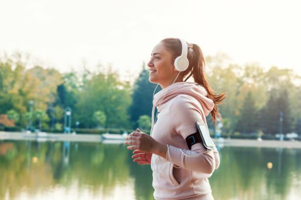 joggen und lächeln - motivationsmusik stock-fotos und bilder