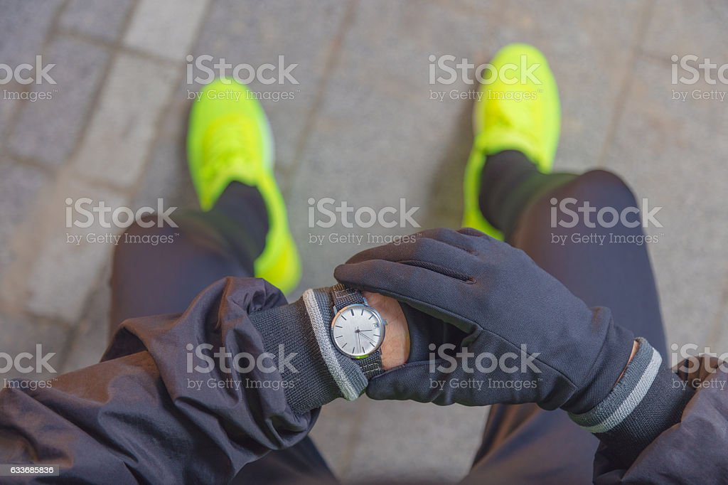 Jogger checking his running time. stock photo