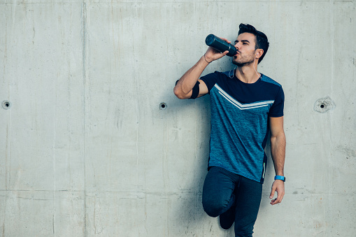 Attractive sportsman drinking water in front of a wall.