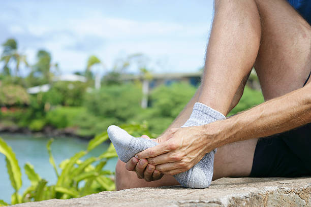 Jogger massaging the metatarsal area of the foot Typical pain in the metatarsal region of a jogger. gout stock pictures, royalty-free photos & images