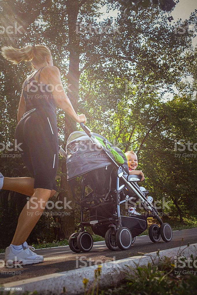 Jogger mom with baby in stroller royalty-free stock photo