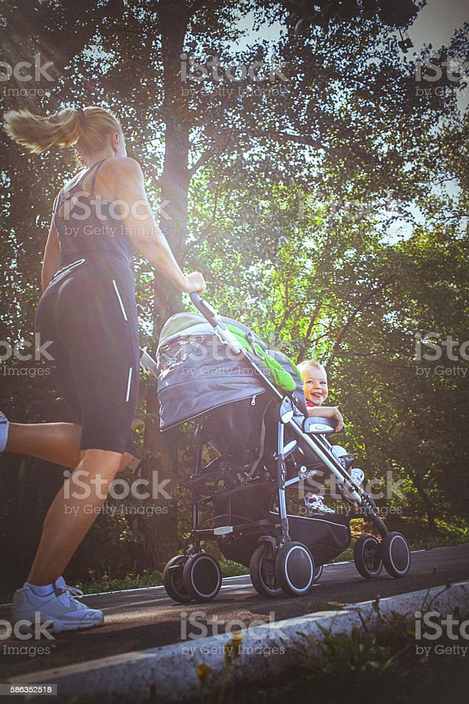 Jogger mom with baby in stroller stock photo