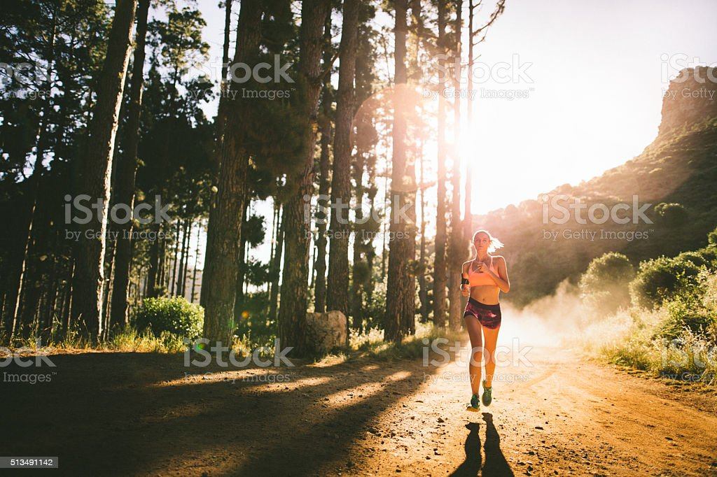 Jogger on a dirt path on a mountain nature trail stock photo