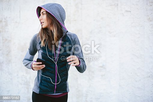 Young woman in sports wear, listening music from her smart phone while running, with copy space