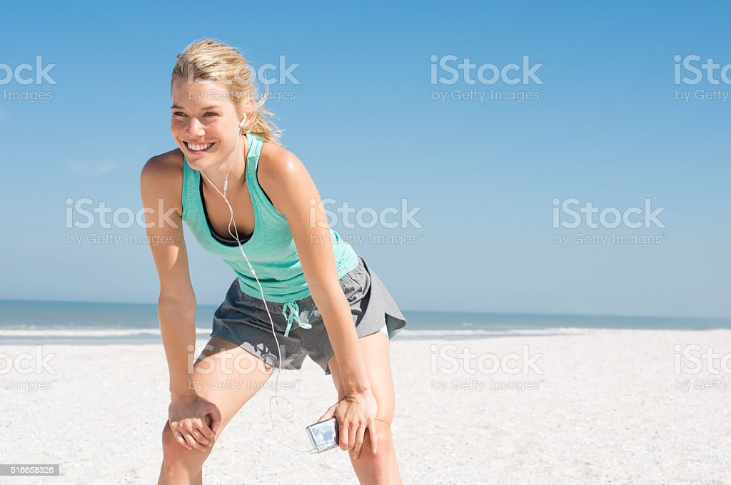 Jogger resting at beach stock photo