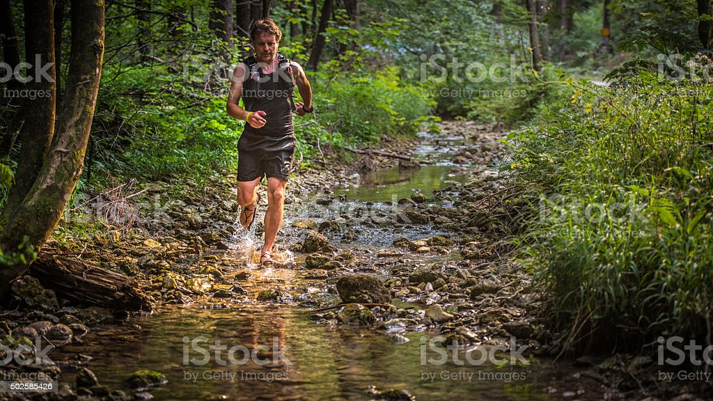 Jogger running downstream in a forest stock photo