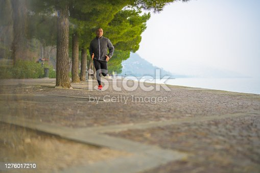 Front view of a jogger running next to some trees on a footpath next to the sea.