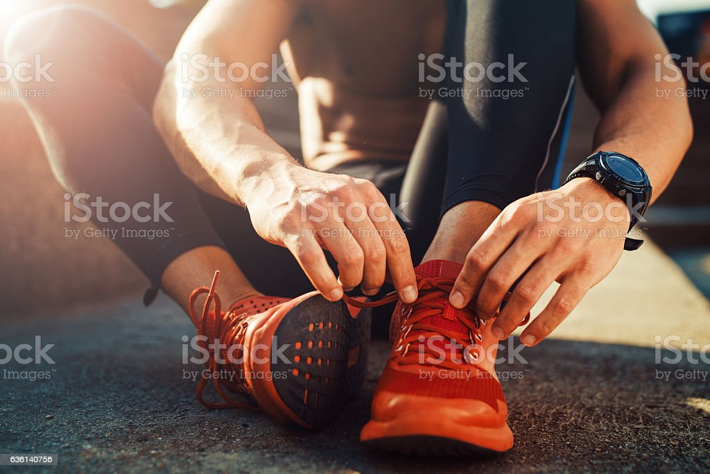 Jogger tying shoe before jogging stock photo