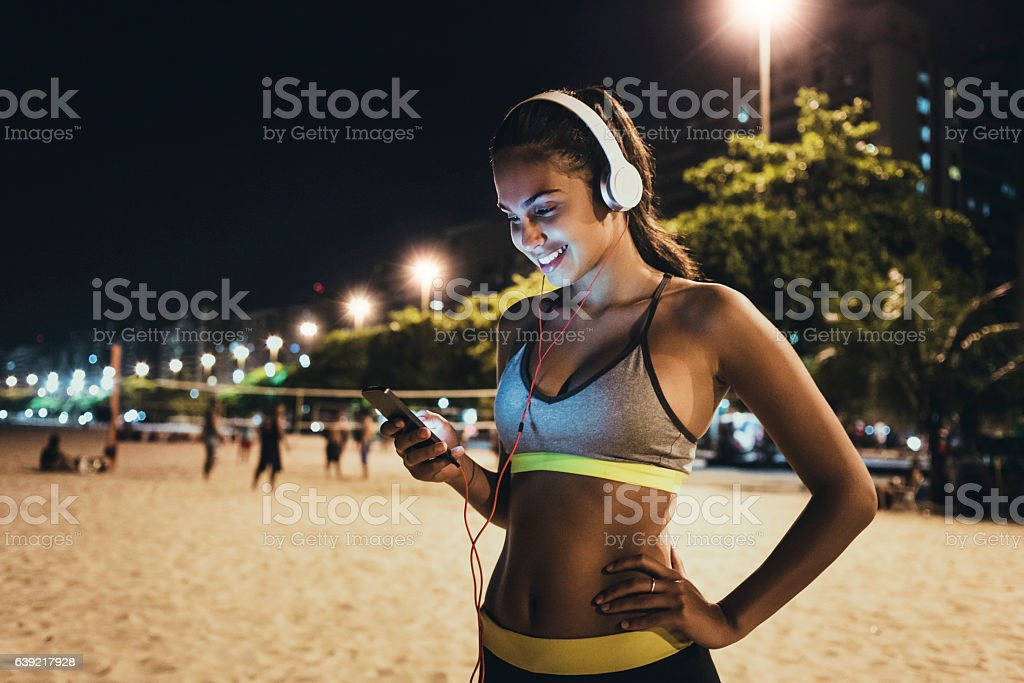 jogger using her smartphone and resting stock photo