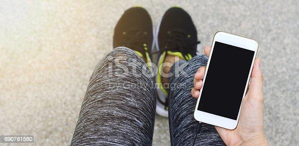 istock Jogger using smart phone, Female runner holding cell phone while taking break. 690761580