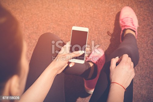 istock Jogger using smartphone on running track 678158026