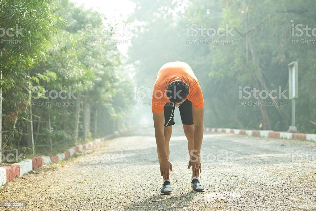 Jogger warming up at park stock photo