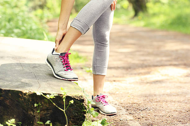 jogger with hurt ankle - human foot stock photos and pictures