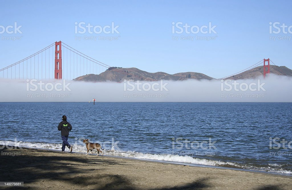 jogging along the beach with dog royalty-free stock photo