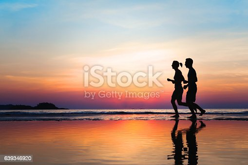 istock jogging and healthy lifestyle, couple of runners silhouettes on beach 639346920