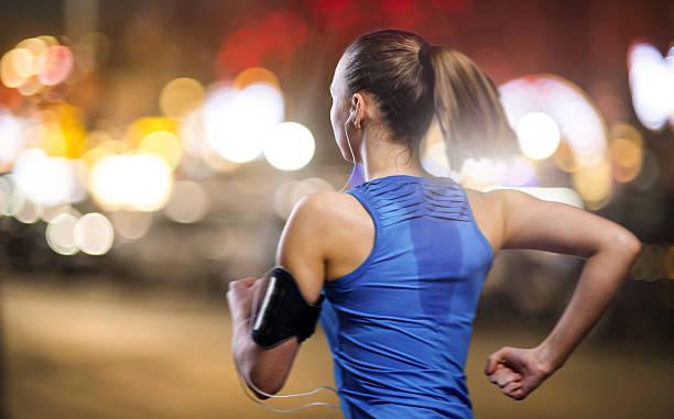 joggen bei nacht - joggerin stock-fotos und bilder
