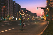 Young woman running at night through city