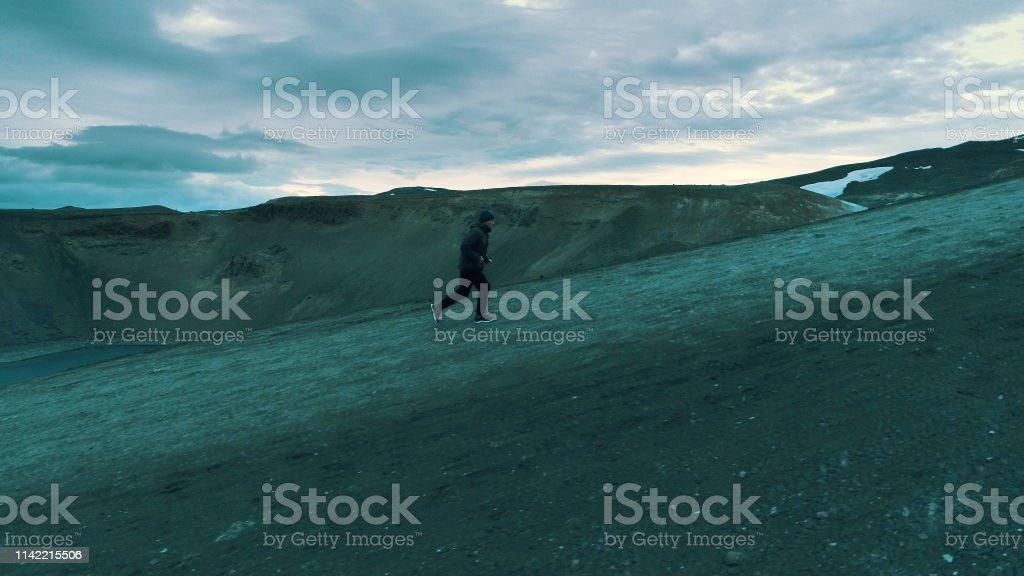 Man running along crater lake edge. Aerial view