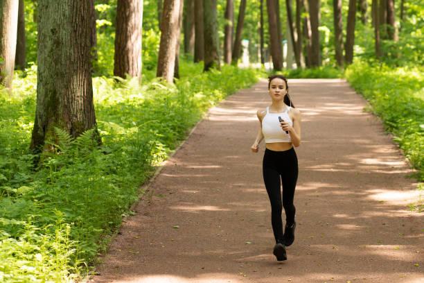 Jogging in nature. Girl in headphones runs in the park, smiling stock photo