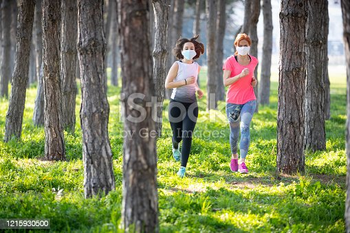Teenage girl running in the woods with her mother, both wearing protective masks during the Covid-19 outbreak