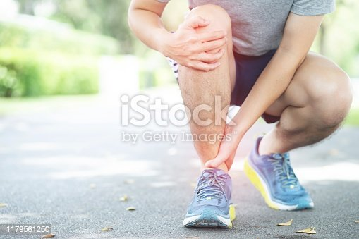 istock Jogging, leg painThe  took the hand to the ankle with motion pain 1179561250