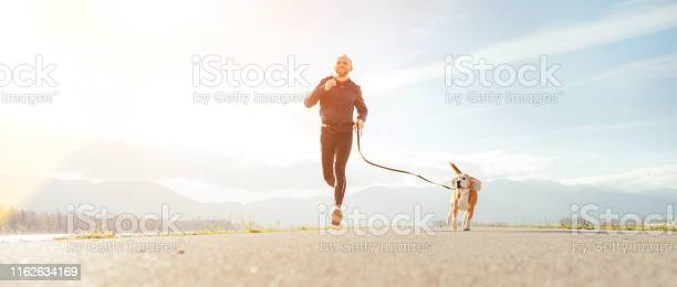 Jogging man with his dog in the morning active healthy lifestyle picture id1162634169?b=1&k=6&m=1162634169&s=612x612&h=hhum9scpsc pqezadda2fss10kiofloke4bmcox8jig=
