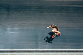Top view of young woman jogging on the street