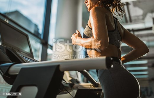 Unrecognizable athletic woman running on treadmill in a health club.
