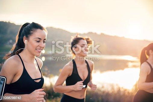Young women running near lake