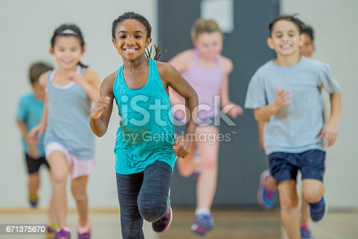 A group of elementary school children of various ethnicity are in PE class. They are indoors in the gym. They are playing a running game and smiling. A young girl of African descent is at the front.