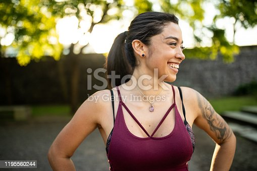 Beautiful smiling Latin woman in sport wear looking away , standing in public park in good mood