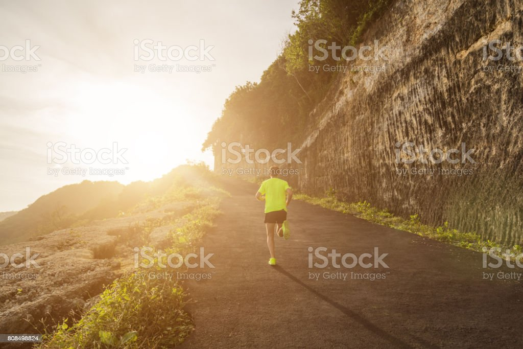 Jogging / running up the hill at sunset / sunrise. stock photo