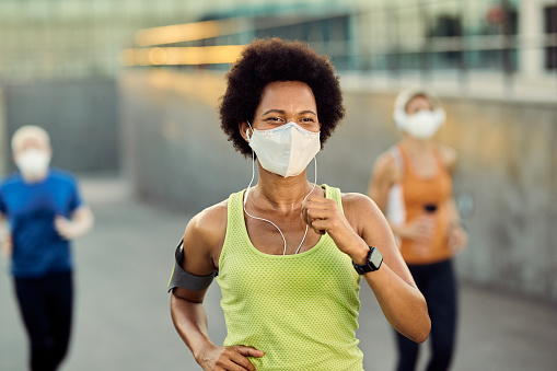 Happy African American female runner wearing protective face mask while jogging outdoors during coronavirus epidemic. There are people in the background.
