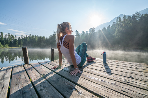 istock Jogging woman relaxing on lake pier at sunrise enjoying freshness from nature 1090246106